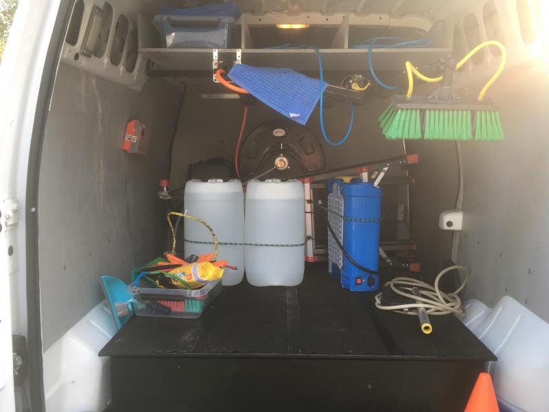 Bedrijfswagen met osmose tank, slangen en borstels.