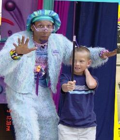 Child joins  Fab Feno on stage to perform magic.